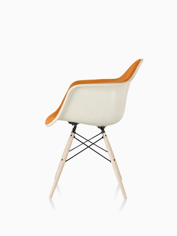 Orange Eames Molded Fiberglass armchair with full upholstery and dowel legs, viewed from the side.