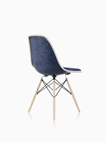 Three-quarter rear view of a blue upholstered Eames Molded Fiberglass side chair with dowel legs.