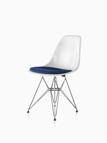 White Eames Molded Fiberglass side chair with a blue upholstered seat pad and a wire base, viewed from a 45-degree angle.