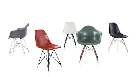 Three Eames Molded Fiberglass Chairs: green side chair, blue armchair, and yellow upholstered side chair.