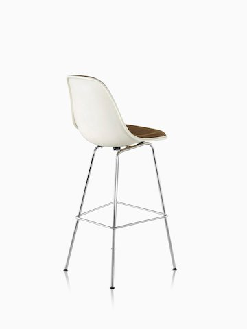 Three-quarter rear view of a white Eames Molded Fiberglass Stool with brown upholstery.