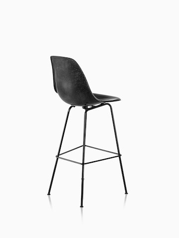 Three-quarter rear view of a black Eames Molded Fiberglass Stool.
