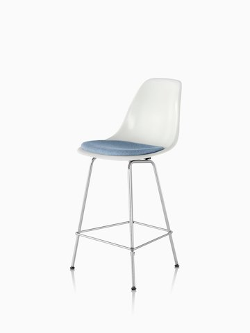 White Eames Molded Fiberglasss Stool with a light blue seat pad, viewed from a 45-degree angle.