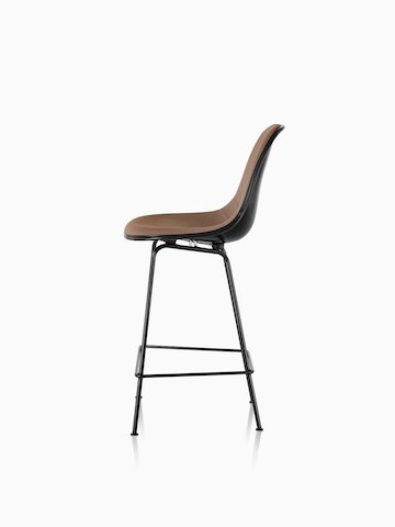 Profile view of a black Eames Molded Fiberglass Stool with brown upholstery.