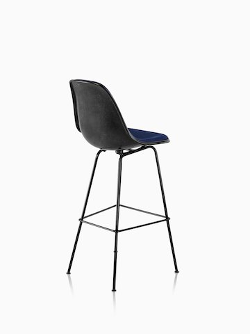 Three-quarter rear view of a black Eames Molded Fiberglass Stool with blue upholstery.