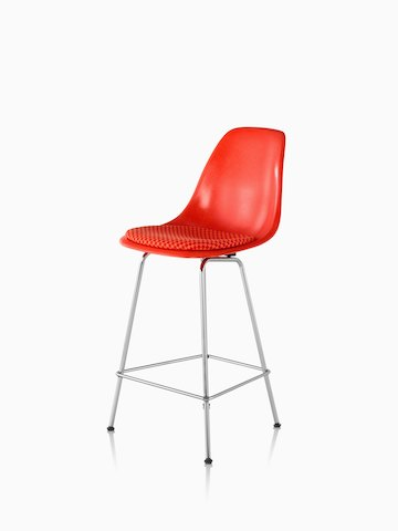 Red Eames Molded Fiberglass Stool with a red seat pad, viewed from a 45-degree angle.