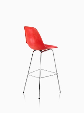 Three-quarter rear view of a red Eames Molded Fiberglass Stool.