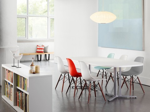 Open meeting area featuring, red, white, gray, and blue Eames Molded Plastic side chairs with dowel legs.