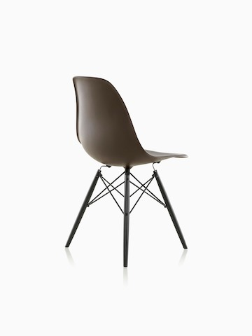 Three-quarter rear view of a black Eames Molded Plastic side chair with dowel legs.
