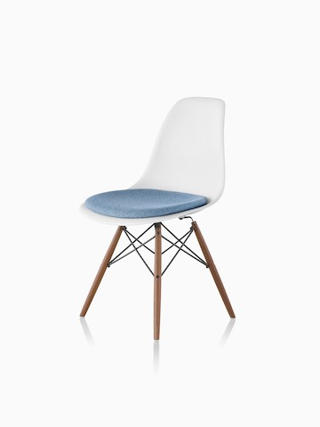 White Eames Molded Plastic side chair with a blue upholstered seat pad and dowel legs, viewed from a 45-degree angle.