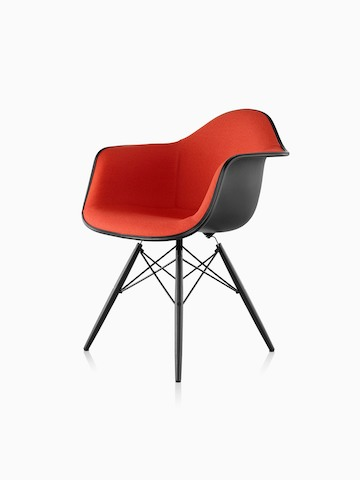Red upholstered Eames Molded Plastic armchair with dowel legs, viewed from a 45-degree angle.