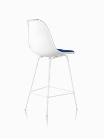 Three-quarter rear view of a white Eames Molded Plastic Stool with blue upholstery.