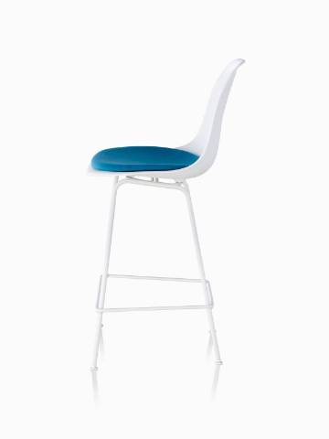 Profile view of a white Eames Molded Plastic Stool with a blue seat pad.