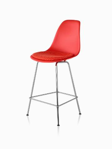 Red Eames Molded Plastic Stool with a red seat pad, viewed from a 45-degree angle.