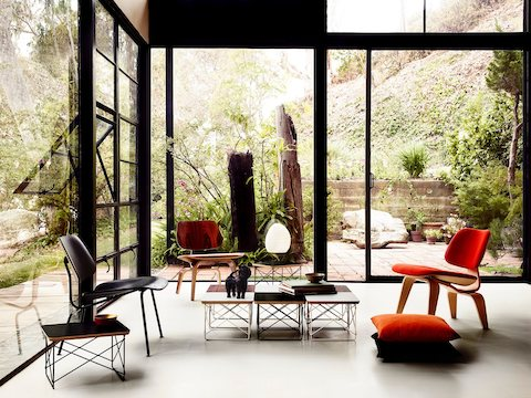 A glass-walled residential lounge with garden views, featuring three Eames Molded Plywood Chairs in various styles.