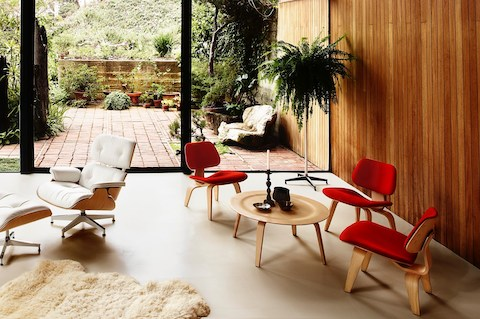 Three red-upholstered Eames Molded Plywood Chairs and a white Eames Lounge Chair overlook the outdoors.