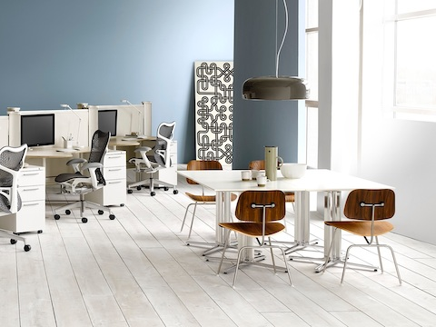 Medium-tone Eames Molded Plywood Chairs and white Everywhere Tables in a casual meeting space.
