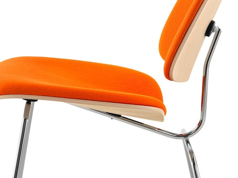 Close profile view of an Eames Molded Plywood Chair with orange upholstery and chrome-plated legs.