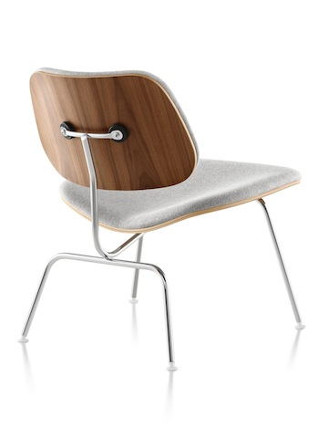 Three-quarter rear view of a gray-upholstered Eames Molded Plywood Chair with chrome-plated legs.