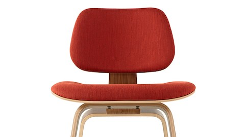 Close view of the upper half of an Eames Molded Plywood Chair with red upholstery.