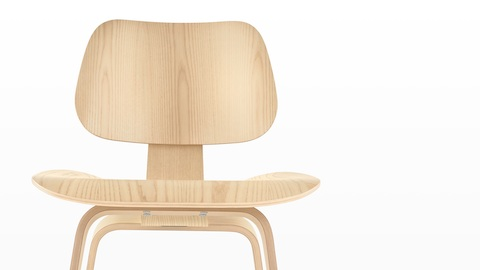 Close view of the upper half of an Eames Molded Plywood Chair with a light finish.
