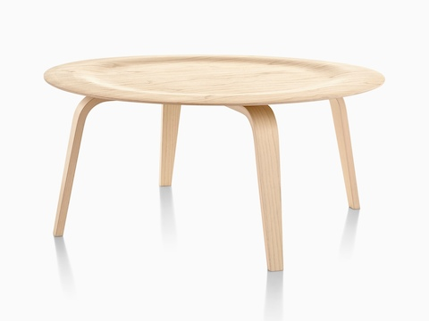 A round Eames Molded Plywood Coffee Table with wood legs and an indented top in a light finish.