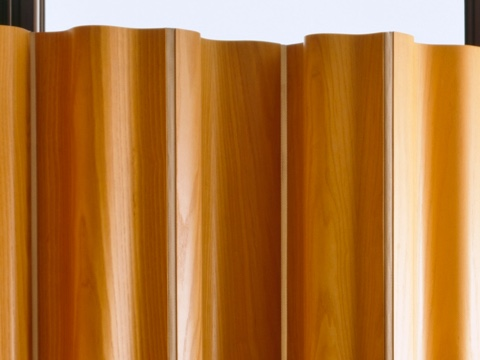 The upper portion of an Eames Molded Plywood Folding Screen in a medium wood finish.
