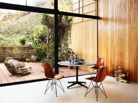 Three Eames Molded Wood side chairs and a round Eames Table in a glass-walled room overlooking a garden.