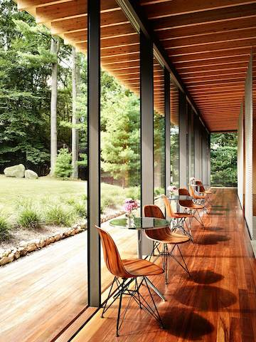 A series of Eames Molded Wood side chairs with wire bases surround bistro tables overlooking the outdoors.
