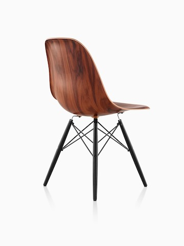 Three-quarter rear view of an Eames Molded Wood side chair with a dark finish and dowel legs.