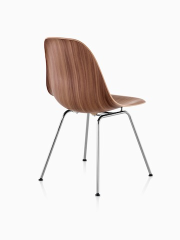 Three-quarter rear view of the four-leg version of an Eames Molded Wood side chair finished in a medium tone.