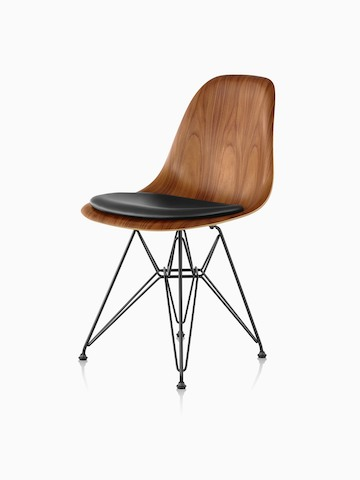 Eames Molded Wood side chair with a medium finish, black seat pad, and wire base, viewed from a 45-degree angle.