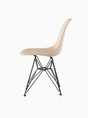 Profile view of an Eames Molded Wood side chair with a light finish and wire base.