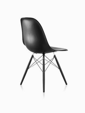 Three-quarter rear view of a black Eames Molded Wood side chair with dowel legs.