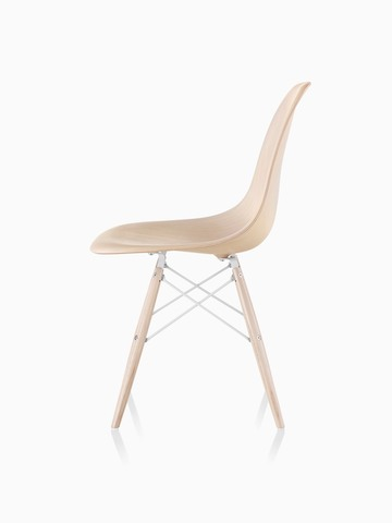 Profile view of an Eames Molded Wood side chair with a light finish and dowel legs.