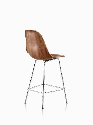 Three-quarter rear view of an Eames Molded Wood Stool with a medium finish and silver legs.
