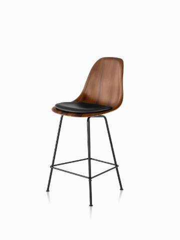 Eames Molded Wood Stool with a dark finish, black leather seat pad, and black legs, viewed from a 45-degree angle.