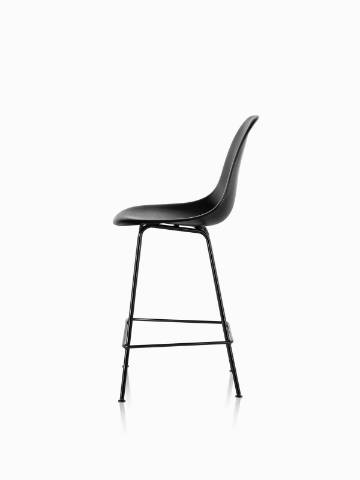 Profile view of a black Eames Molded Wood Stool with black legs.