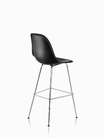Three-quarter rear view of a black Eames Molded Wood Stool with silver legs.
