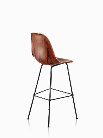 Three-quarter rear view of an Eames Molded Wood Stool with a dark finish and black legs.