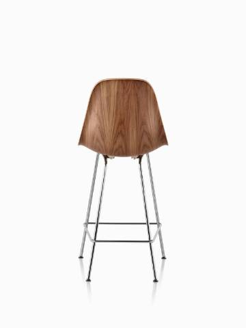 Eames Molded Wood Stool with a medium finish and silver legs, viewed from the rear.