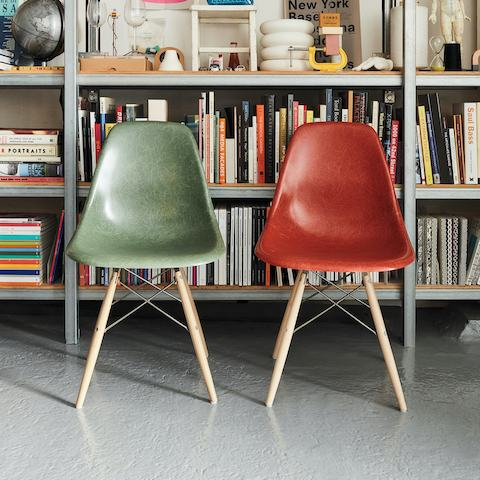 Two Eames Moulded Fibreglass Side Chairs sitting in front of a bookshelf.