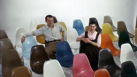 An archival image of Charles and Ray Eames sitting in a room full of colourful Shell Chairs.