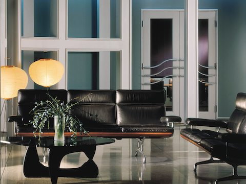 A black leather Eames Sofa, an Eames loveseat, and a Noguchi Table in an office lobby.