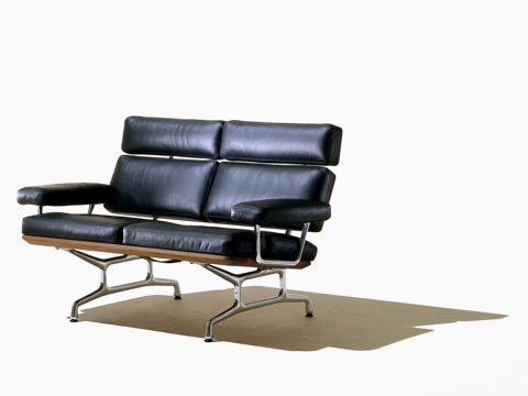 Angled view of a black leather Eames loveseat with polished aluminum legs and arm supports.
