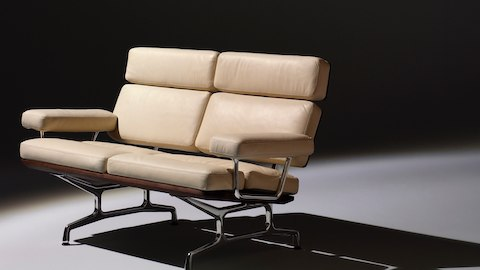 Angled view of an ivory-colored Eames loveseat, showing the thick cushions on the seat, back, and arms.