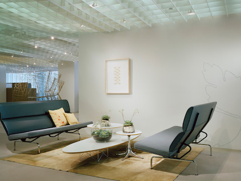 Two gray Eames Sofa Compacts facing each other in an office lobby.