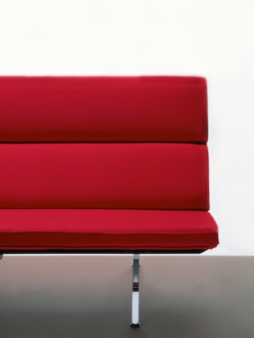 Partial front view of a red Eames Sofa Compact, showing the minimalist mid-century style.