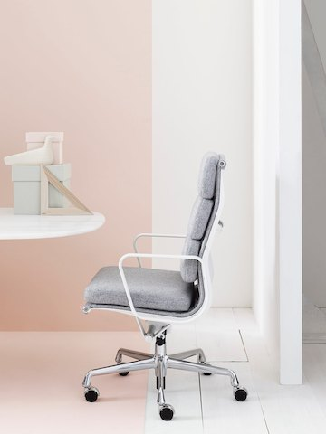 Profile view of Eames Soft Pad high-back executive chair in light gray upholstery.