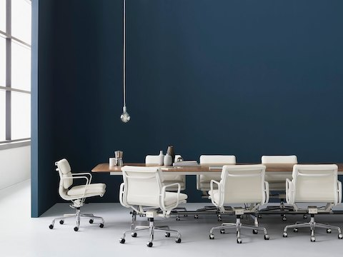 White leather Eames Soft Pad Chairs around a rectangular conference table.
